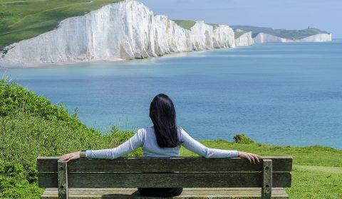Femme de dos assise regardant la mer